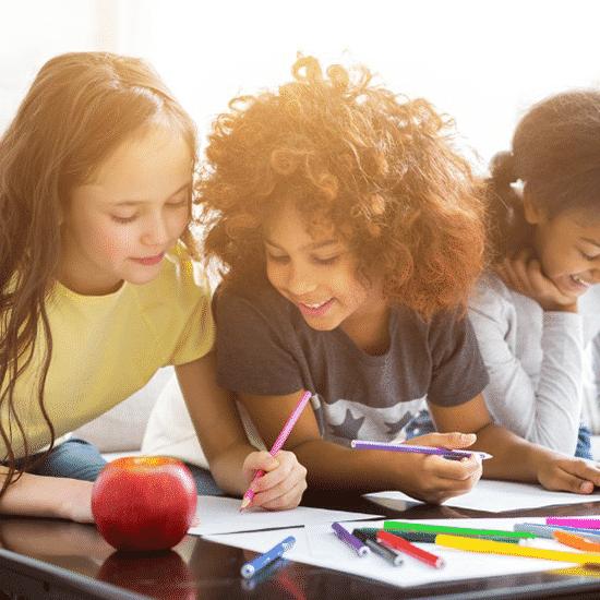 three children sitting around a desk and drawing some art